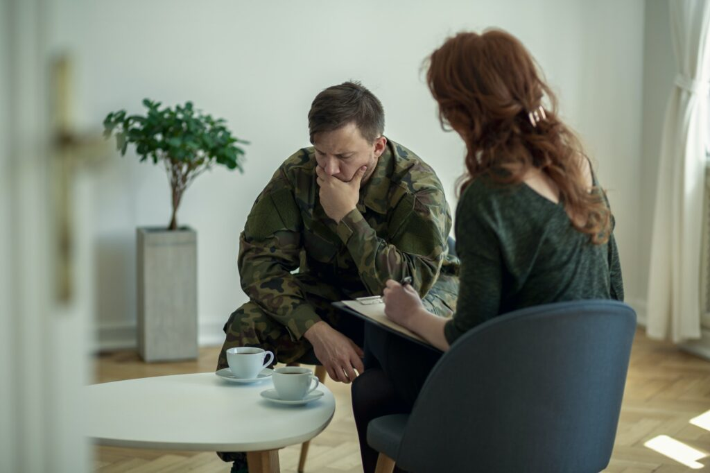 Sad soldier covering his mouth while talking to his therapist