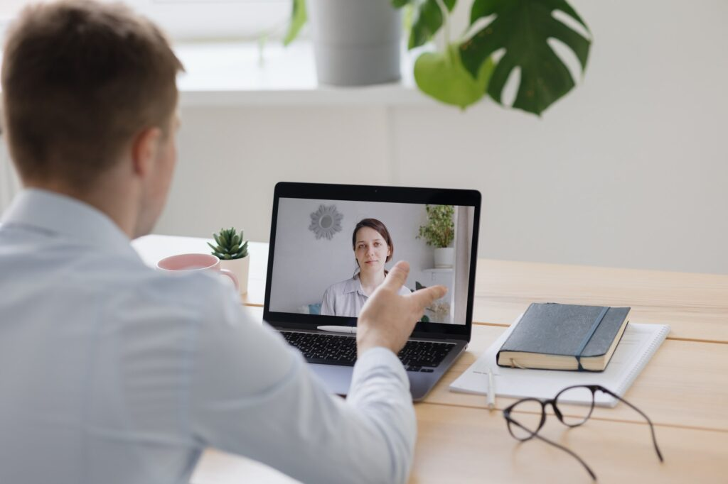 telemedicine, a doctor in a white coat and glasses communicates with a patient online via webcam